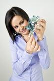 Young woman saving money. Medium shot of a smiling woman saving money in a blue piggy bank Royalty Free Stock Photo