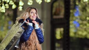 Smiling young European female holding shopping bags gifts at Christmas golden lights background stock video footage