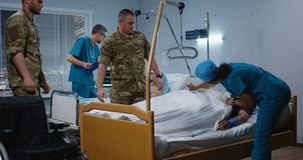 Injured soldiers in hospital among doctor and nurse. Medium shot of soldiers helping their fellow getting to bed in hospital among doctor and nurse stock video