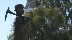 A statue of a miner with trees