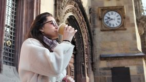 Medium shot female tourist drinking paper coffee cup admiring amazing medieval architecture. Medium shot stylish female tourist drinking paper coffee cup stock footage