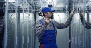 Technician searching through cables. Medium shot of a technician searching through cables at a data center stock photography