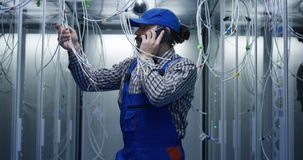 Technician works talking on phone in data center. Medium shot of technician working with cables in a data center full of rack servers running diagnostics and royalty free stock image