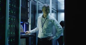 Technicians work on a laptop in a data center. Medium shot of technicians working on a laptop in a data center full of rack servers running diagnostics and stock photos