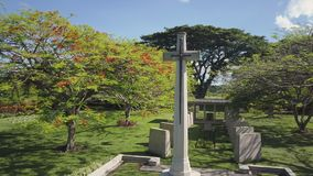 A cemetery tombstone with green fields and trees