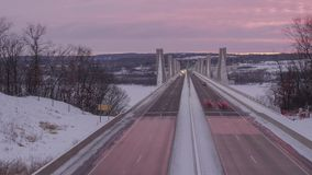 A medium shot on traffic driving over the St. Croix Crossing Bridge between Minnesota and Wisconsin during a Dramatic Winter Sunse. A dramatic sunset timelapse stock video footage