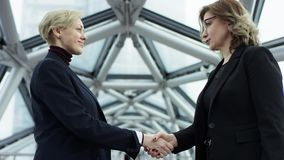 Medium shot of two beautiful women standing in an office hall, then shaking her hand in agreement. they are wearing. Formal clothes. They meet after work stock footage