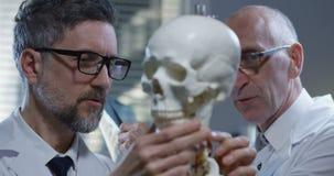 Doctors analyzing x ray on skeleton. Medium shot of two doctors analyzing x ray on skeleton stock video