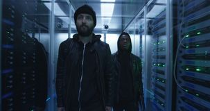 Two hackers walking through rows of servers. Medium shot of a two hackers walking through corporate data center with rows of working rack servers stock video footage