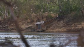 Docking station with a few boats. Medium shot of two small boats docked at a docking station with a caravan parks in the background stock footage