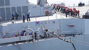 Medium Shot US Navy Fuel Pipe Connect Ship. US Navy. A fuel pipe witch is conntact another ship is pulled by soldiers stock video footage