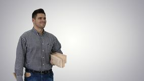 Brunette man builder with planks is ready to build something on gradient background. stock video footage