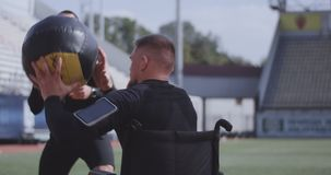 Wheelchaired athlete and trainer throwing medicine ball. Medium shot of a wheelchaired athlete and his trainer working out with a medicine ball stock footage