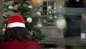Medium shot of woman and man hanging decorations on Christmas tree stock video