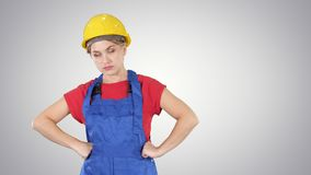 Woman with protective helmet showing fist to camera Did something wrong on gradient background. Medium shot. Woman with protective helmet showing fist to camera stock video