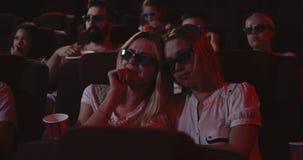 Women watching sad movie in cinema. Medium shot of women getting emotionally affected while watching sad movie in cinema stock video footage