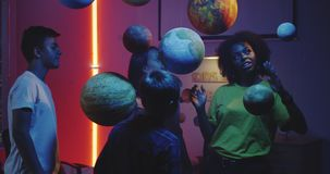 Teacher explaining astronomy to students. Medium shot of a young female teacher explaining astronomy to students with planet models stock video footage