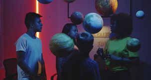 Teacher explaining astronomy to students. Medium shot of a young female teacher explaining astronomy to students with planet models stock footage