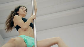 Medium shot Young girl dancing poledance in white room stock video footage
