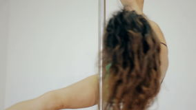 Medium shot Young girl dancing poledance in white room stock video