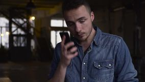 Medium shot of a young guy talks on the phone in a big dark hall.  stock video