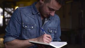 Medium shot of young handsome gay man writing on notepad in a big dark hall.  stock video