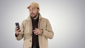 Young man making a video call from his mobile phone while walking on gradient background. Medium shot. Young man making a video call from his mobile phone while stock photography