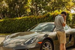 Medium shot of a young man at the phone, standing close to a Porsche Cayman. Urban scene. MIAMI, USA - APRIL 30, 2016: Medium shot of a young man at the phone royalty free stock images