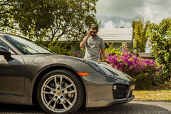 Medium shot of a young man at the phone, standing by a Porsche C. MIAMI, USA - APRIL 30, 2016: Medium shot of a young man at the phone, standing by a Porsche royalty free stock images