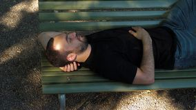 Young man sleep on a bench. Medium shot.Young man sleep on a bench. Professional shot in 4K resolution. 02. You can use it e.g. in your commercial video stock video footage