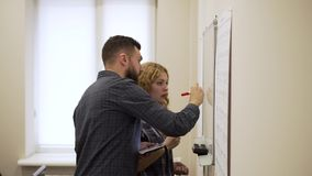 Medium shot of Young man and woman draw a graph on white board in office