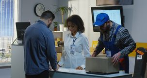 Man sending a package in a delivery center. Medium shot of a young men sending a package in a delivery center stock images