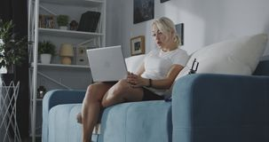 Woman having a video call. Medium shot of a young woman having a video call on a laptop while sitting on a sofa at home stock footage