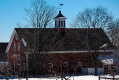 Medium size red New England Barn on a snowy field against a deep blue late winters sky. Red cupola with white trim on top, weather vane, surrounded by multiple royalty free stock photos
