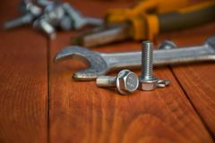 Bolt emphasis . Closeup of a wrench with bolts on a wooden table royalty free stock photos