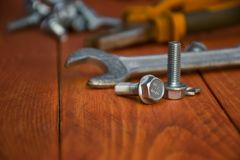 Closeup of a wrench with bolts on a wooden table royalty free stock images