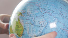 Medium-sized globe with human hands looking with a magnifying glass on a black background. stock video footage