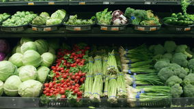 Medium tracking shot of vegetables in a grocery store stock video footage