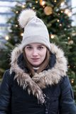 Young woman in fur trimmed black winter coat with lighted Christmas tree in soft focus background. Medium vertical shot of pretty smiling young woman in fur Royalty Free Stock Photos