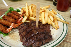 Medium well. Steak, shrimps and fries Royalty Free Stock Photography