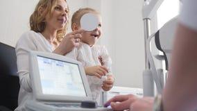 Medizin für Kinder - Optometriker in der Klinik kleines Mädchen ` s Vision überprüfend lizenzfreie stockfotografie