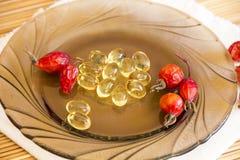 medizin Medikationen und Vitamine Kapseln mit Hagebuttenöl und -Trockenfrüchten Lizenzfreies Stockbild