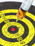 Medizin-Spritze fest in altes gelbes Ziel-Brett Stockbilder