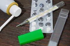 Medizin- und Diagnostikkälten Mercury-Thermometer, Antibiotika und eine Kehle sprühen Lizenzfreies Stockfoto
