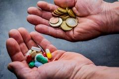 Medizin und Geld in den menschlichen Händen stockbild