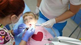 Medizin und Gesundheitswesen, Kind mit den schmerzenden Zähnen liegt auf zahnmedizinischem Lehnsessel an der Behandlung mit Dokto stock footage