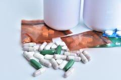 Medizin und weiße Plastikflasche auf weißem Hintergrund Lizenzfreie Stockbilder