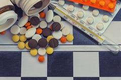 Medizin wird auf das Schachbrett zerstreut lizenzfreie stockfotografie