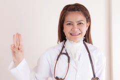Medizindoktorfrau, die Geste drei zeigt Stockfoto