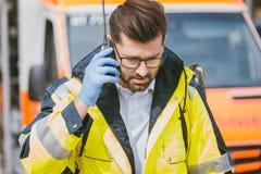 Mediziner, der mit Hauptsitz über Radio vor Krankenwagen spricht Lizenzfreie Stockfotos